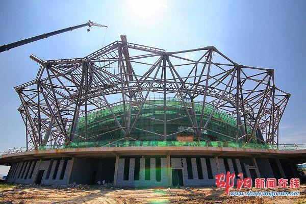 """邵阳新闻在线讯(记者 罗哲明)8月4日,""""莲花""""造型的市体育中心项目1号馆已初具雏形。建设用地面积为32.2公顷的市体育中心项目包括""""两场三馆一体校"""",即30000座位的主体育场、17万平方米的全民健身广场、6000座位的主体育馆、8赛道的标准游泳馆、6000平方米的综合训练馆以及400人规模的体育运动学校。目前,该项目体育馆主体钢结构已全部完成,正在做屋面和玻璃幕墙。整个工程预计年底完工。图为主体育馆""""雏形""""。  体育馆场内天"""